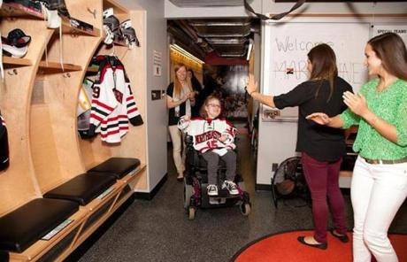 Hockey team members greet Marianne in the locker room.